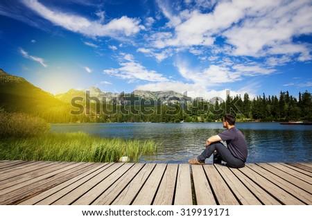 Man sitting on the bank of alpine mountain lake - stock photo