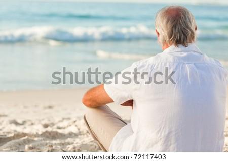 Man sitting on the beach - stock photo