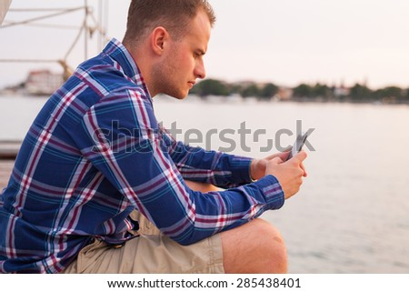 Man sitting on the bridge next to sea and using tablet - stock photo