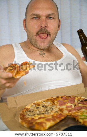 Man sitting on the couch with a pizza and a bottle of beer
