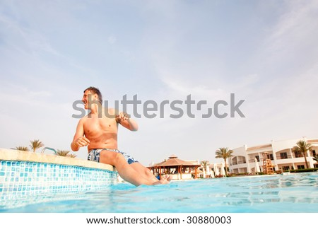 Man sitting on the edge of swimming pool. Low angle view from water surface. - stock photo