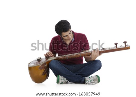 Man sitting on the floor and playing a sitar