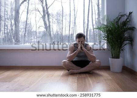 Man sitting on the floor in cross legged position - stock photo