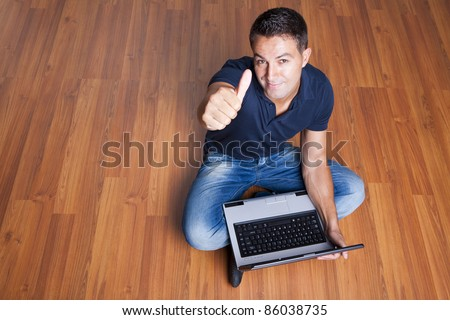 man sitting on the floor with laptop and with his thumb up