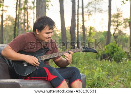 Man sitting on the sofa guitar in forest green.