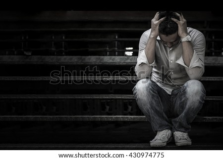 Man sitting on the stairs are saddened and frustrated with life./made picture to the concept - stock photo