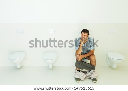 Man sitting on the toilet, public bathroom - stock photo