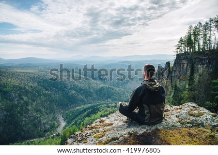 Man sitting on the top of the mountain and contemplates amazing and beautiful view of the valley - stock photo