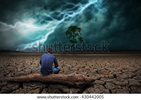 Man sitting on timber on land to the ground dry cracked and big tree. With lightning storm - stock photo