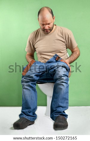 Man sitting on toilet with diarrhea caused by stomach flu - stock photo