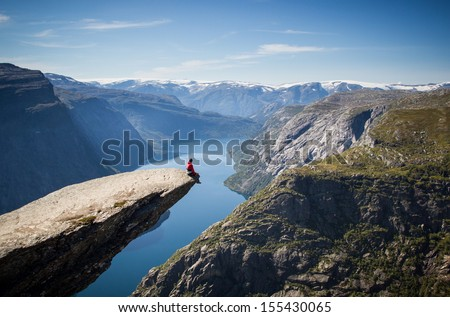 man sitting on trolltunga in norway  - stock photo