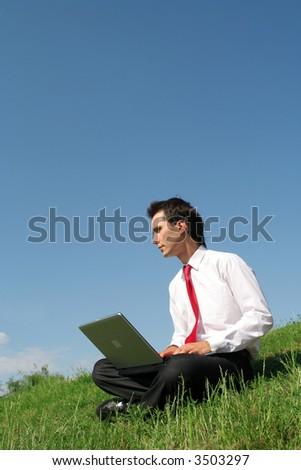 Man sitting outdoors using laptop - stock photo