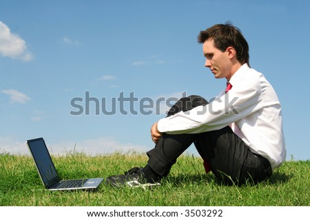 Man sitting outdoors with laptop - stock photo