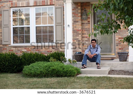 man sitting outside his new house