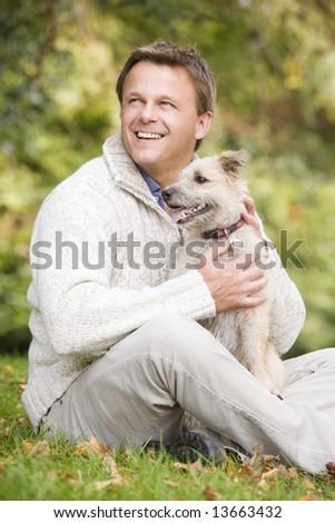 Man sitting outside holding pet dog - stock photo
