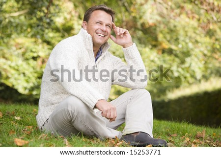 Man sitting outside on grass in autumn landscape - stock photo