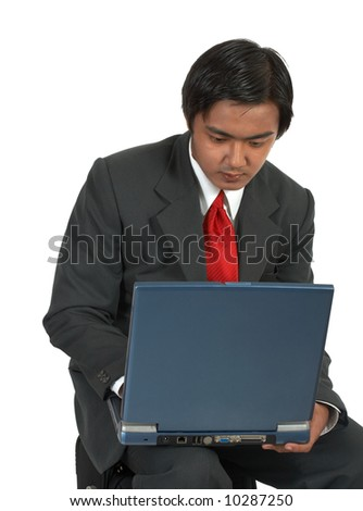 man sitting while working on his laptop computer - stock photo