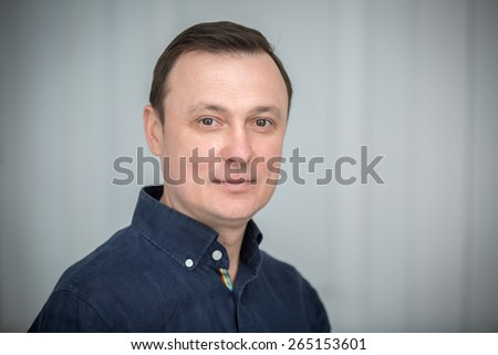 Man sitting with a slight smile and looking at the camera. Studio in the Kiev, Ukraine. - stock photo
