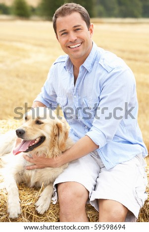 Man Sitting With Dog On Straw Bales In Harvested Field - stock photo