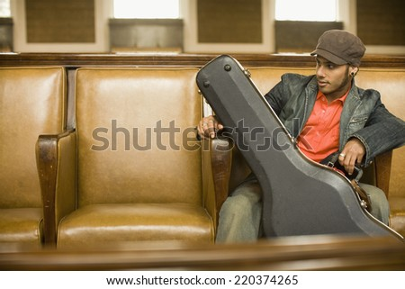 Man sitting with guitar case - stock photo