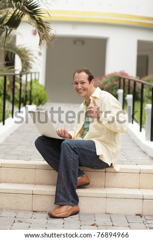 Man sitting with his notebook computer - stock photo