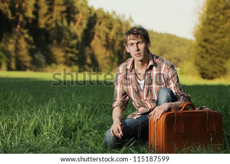 Man sitting with his suitcase in grass Casual young man kneeling alongside his suitcase in a green grass field in evening light