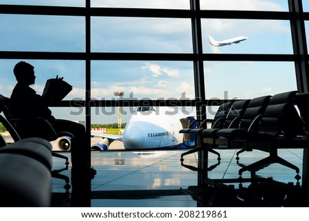 Man sitting with magazine in airport. Jetliner on the background.