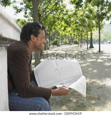 Man sitting with newspaper in urban park