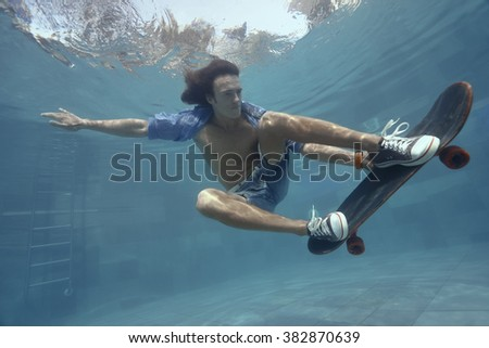 Man skateboarding underwater in the swimming pool