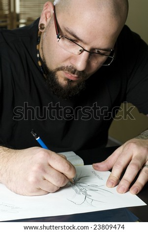 Man sketching on table preparing a tattoo - stock photo