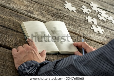 Man sketching two matching puzzle pieces in his notepad with various puzzle pieces lying on his wooden textured desk. Conceptual of education, research, solution making and innovation. - stock photo