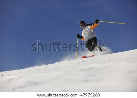 man ski free ride downhill at winter season on beautiful sunny day and powder snow - stock photo