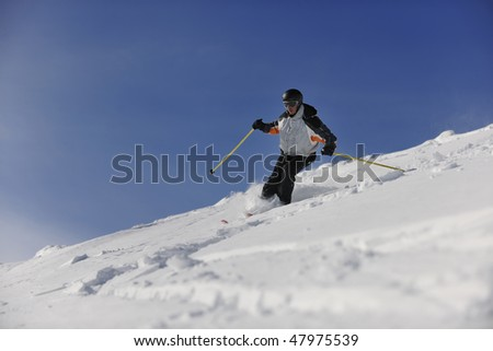 man ski free ride downhill at winter season on beautiful sunny day and powder snow