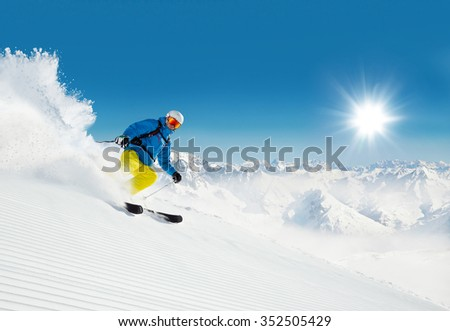 Man skier running downhill on sunny alpine slope - stock photo