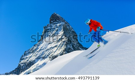 Man skiing in deep fresh powder snow with Matterhorn in background in Swiss Alps.