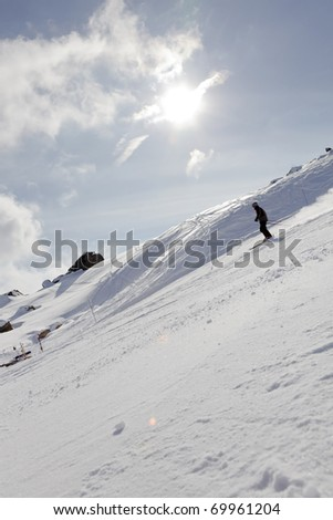 Man skiing on white mountain with sunrays and blue cloudy sky. France. Saint Jean d'Arves. Alpes. - stock photo