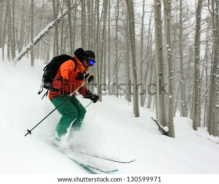 Man skiing powder snow during a snowstorm in an aspen glade, Utah, USA. - stock photo