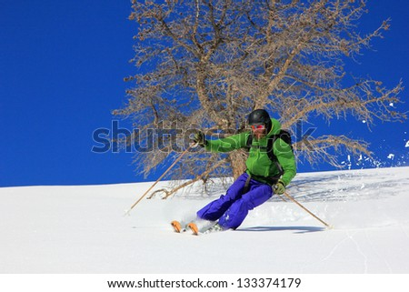 Man skiing with pinion pine in the background. - stock photo
