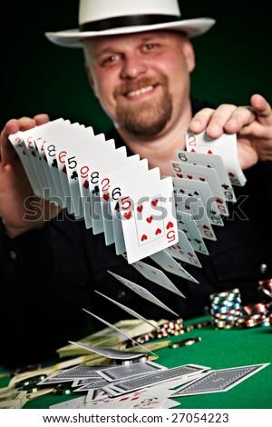 man skilfully shuffles playing cards... - stock photo