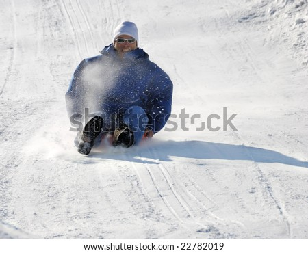 man sledding fast down the hill with snow background - stock photo