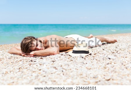 man sleep rest on beach, handsome male sleeping summer vacation, sun tanned body, guy over sea blue sky, ocean holiday travel
