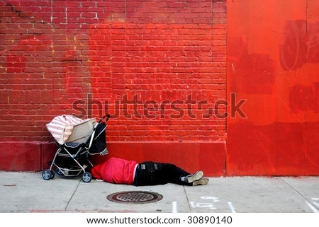 Man sleeping in front of red wall - stock photo