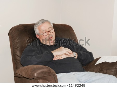 Man sleeping in his lounger chair - stock photo