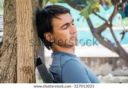 man sleeping, man napping outdoors at noon, relaxation on the nature   - stock photo