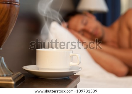 man sleeping on a bed, a cup of hot steaming coffee on the bedside table and lamp - stock photo