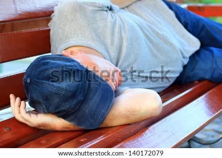 Man sleeping on a bench - stock photo