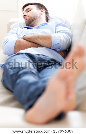 Man sleeping on sofa - stock photo