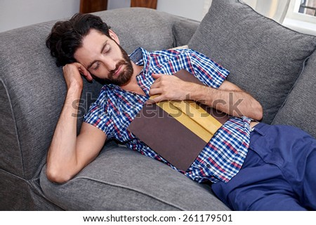 man sleeping on sofa couch while reading book at home living room lounge - stock photo