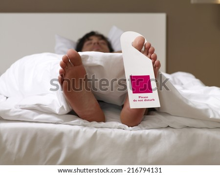 "Man sleeping with a ""do not disturb"" sign on his toe. - stock photo"