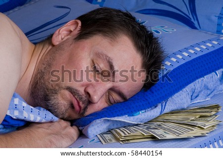 man sleeping with money under his pillow - stock photo
